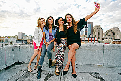 Smiling women posing for cell phone selfie on urban rooftop - p555m1472931 by Peathegee Inc