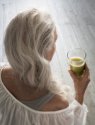 Ältere Frau hält Smoothie - p922m2071565 von Juliette Chretien