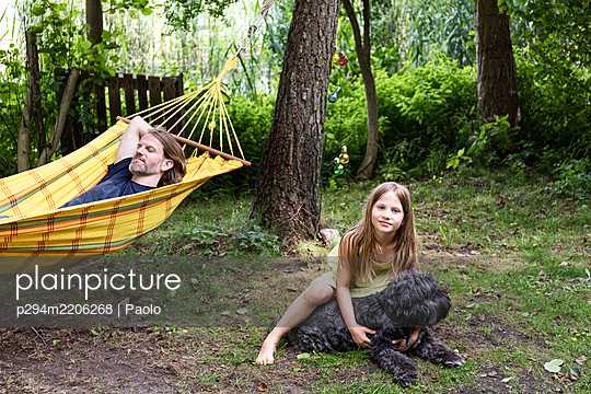 Girl snuggling with dog - p294m2206268 by Paolo