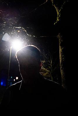 Silhouette eines junges Mannes in der Dunkelheit - p1057m2045500 von Stephen Shepherd