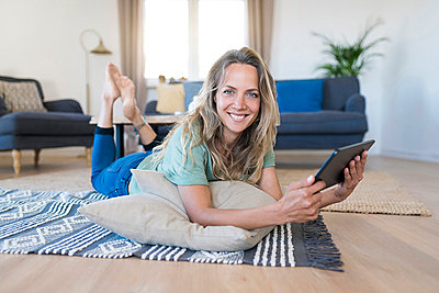 Portrait of smiling woman lying on the floor at home using tablet - p300m2104355 by Steve Brookland