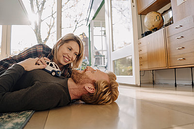 Happy couple lying on the floor at home with toy car - p300m2205535 by Kniel Synnatzschke