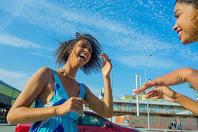 Young woman laughing while looking at female friend in city on sunny day - p300m2239990 by LOUIS CHRISTIAN