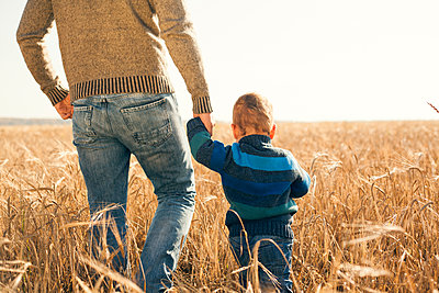 Caucasian father and son walking in rural field - p555m1421421 by Aliyev Alexei Sergeevich