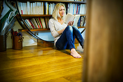 Woman sitting on floor reading book at home - p623m1447786 by Frederic Cirou