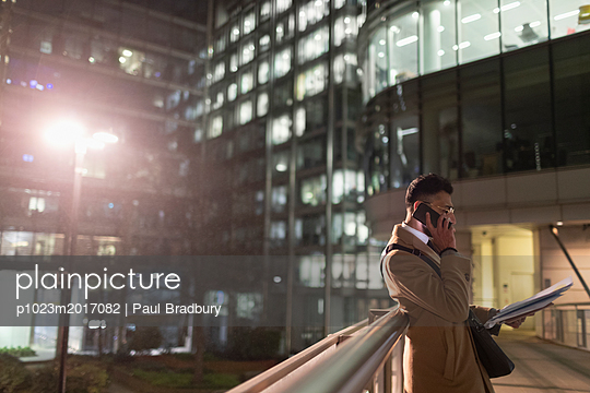 Businessman talking on smart phone, reading paperwork on urban pedestrian bridge at night - p1023m2017082 by Paul Bradbury