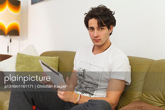 Junger Mann sitzt auf dem Sofa und spielt auf dem Tablet - p1316m1161171 von Christian Kasper