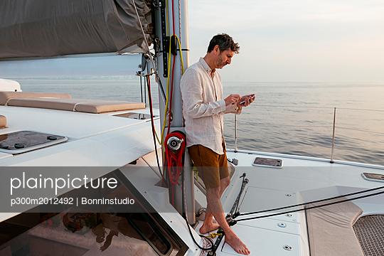Marure man on catamaran, using smartphone - p300m2012492 von Bonninstudio