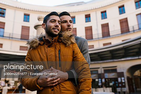 Young man embracing male friend while standing in city - p300m2251677 by Ezequiel Giménez