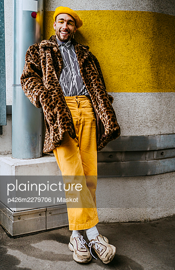Full length of smiling young man with hands in pockets leaning on wall - p426m2279706 by Maskot