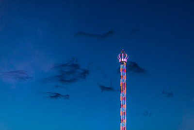 Germany, Bavaria, Munich, Low angle view of Bayern Tower chain swing ride glowing against sky at dusk - p300m2170620 by Michael Malorny