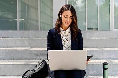 Businesswoman working on laptop while sitting on staircase - p300m2287623 by Francesco Morandini