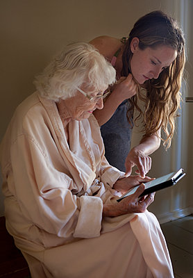 Caucasian caregiver helping older woman use digital tablet - p555m1408804 by Shestock