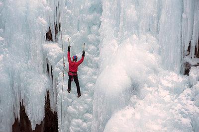 Caucasian man climbing ice - p555m1478019 by Pete Saloutos