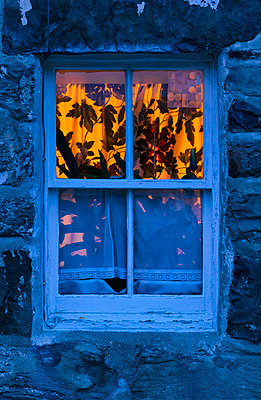 Old stone house cottage window illuminated light warm facade - p609m2066519 by WALSH photography