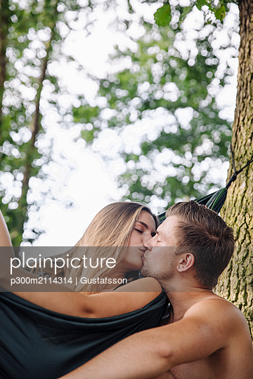 Couple relaxing in hammock by the lake, kissing - p300m2114314 von Gustafsson