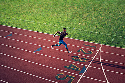 High angle view of male athlete running on field - p1166m1088139f by John Trice