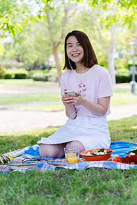 Happy young woman with cell phone and earphones having a picnic in park - p300m2114172 by Francesco Morandini