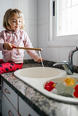 Portrait of little girl fishing rubber ducks in kitchen sink - p300m2189086 by Josep Rovirosa
