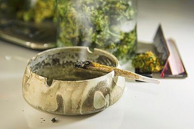Studio, Burning Marijuana joint on ashtray, close up - p300m879133 by realitybites