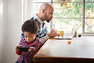 Mixed race father and son using technology at table - p555m1312278 by Sam Diephuis