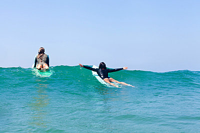 Female friends surfing;  Hermosa Beach;  California;  USA - p924m836611f by Jordan Lutes