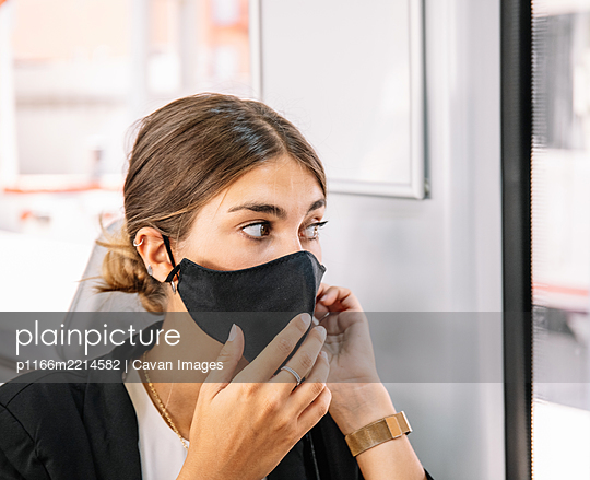 Female with pandemic mask talking on cell phone while commuting to work by train - p1166m2214582 by Cavan Images