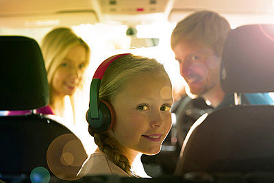 Portrait smiling girl with headphones riding in back seat of car - p1023m2161809 by Himalayan Pics