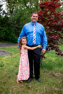 Portrait of happy daughter embracing father while standing on grassy field at park - p1166m2009502 by Cavan Images