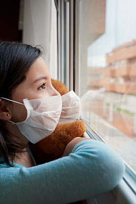 Girl with face mask looking out the window quarantined by coronavirus - p1166m2189767 by Cavan Images