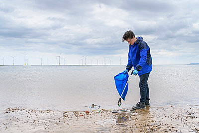 Man using litter picker to remove plastic pollution collected on beach, North East England, UK - p429m2004551 by Monty Rakusen