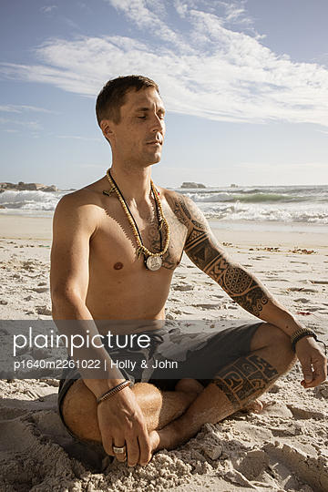 Man practises meditation on the beach in the sunshine - p1640m2261022 by Holly & John
