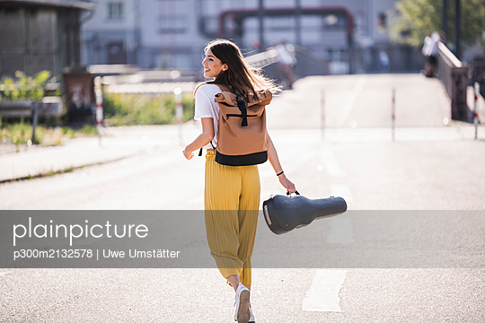 Happy young woman carrying violin case walking on the street - p300m2132578 by Uwe Umstätter
