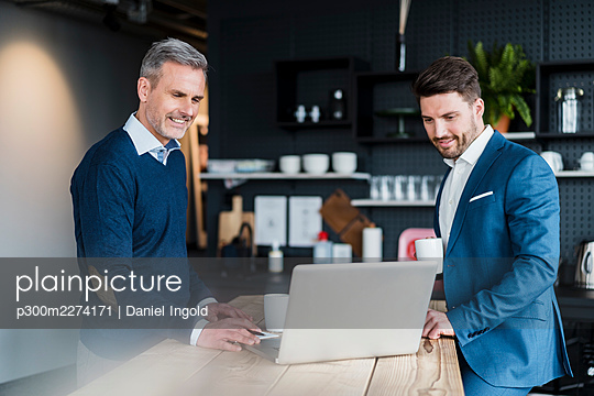 Business people working on laptop in office cafe - p300m2274171 by Daniel Ingold