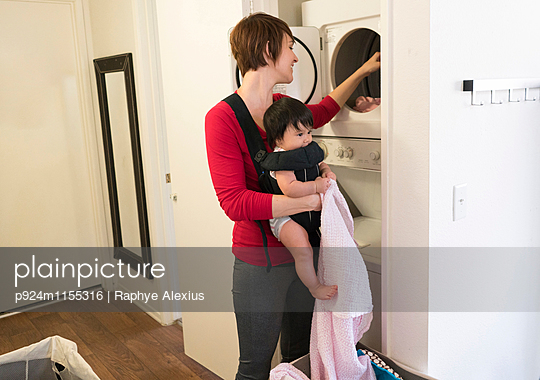 Mother with baby in carrier, doing laundry - p924m1155316 by Raphye Alexius