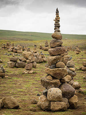 A tall rock cairn made by hikers to mark a spot on a walking path.  - p1100m1067138f by Mint Images