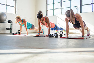 Female athletes doing push-ups on exercise mats in health club - p1166m1422979 by Cavan Images