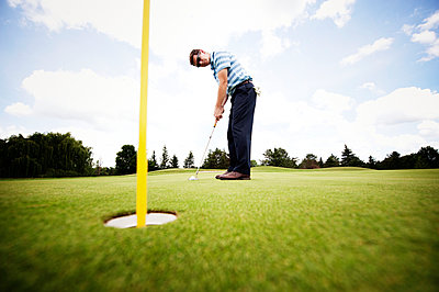Side view of golfer playing on field - p1166m969516f by Cavan Images