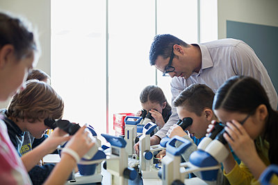 Students and teacher at microscopes science laboratory classroom - p1192m1019853f by Hero Images