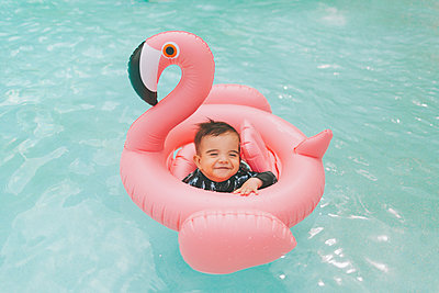 Carefree baby boy in pink flamingo float in swimming pool - p300m2113946 by Crystal Sing
