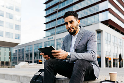 Porrait of a casual young businessman sitting on stairs in the city using tablet - p300m2160171 by Josep Rovirosa