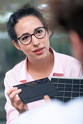 Female entrepreneur with solar panel model looking at male colleague in office - p300m2266002 by Florian Küttler