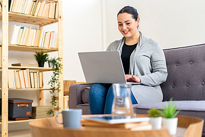 Smiling woman using laptop in living room at home - p300m2274580 by Giorgio Fochesato