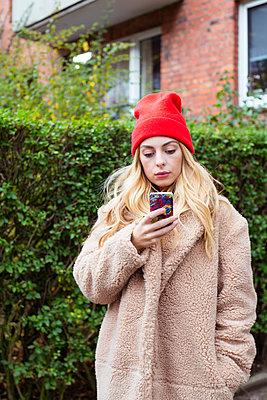 Junge Frau schaut auf ihr Handy - p432m1502404 von mia takahara