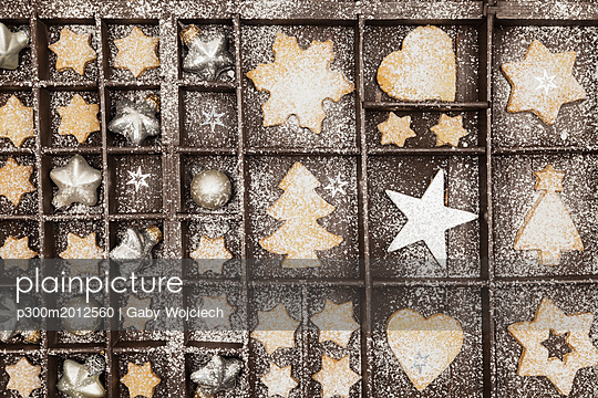 Homemade Christmas cookies, stars and Christmas baubles in old wooden typecase - p300m2012560 von Gaby Wojciech