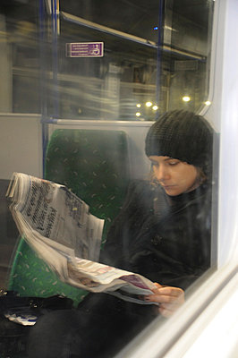 View through window of a train carriage of a woman reading a newspaper - p1072m829393 by Neville Mountford-Hoare