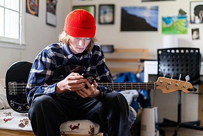 Teenager looking at smart phone while holding bass guitar in bedroom - p1166m2191856 by Cavan Images