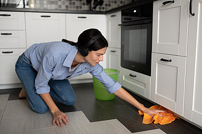 Casual woman listening to music and washing floor in kitchen - p1166m2234848 by Cavan Images