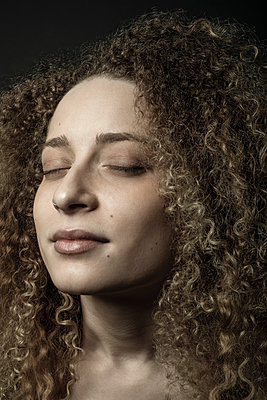 Close up portrait serene beautiful young woman with curly hair - p1192m2065972 by Hero Images
