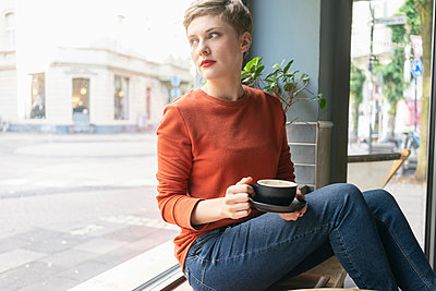 Woman drinking coffee inside shop, Cologne, Nordrhein-Westfalen, Germany - p429m2077940 by Tamboly